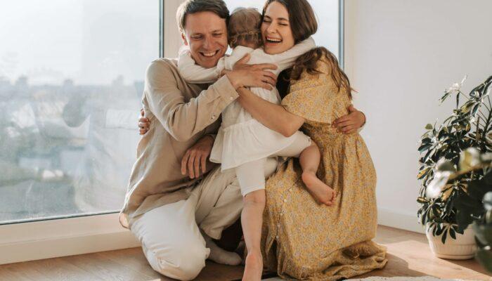 Imagen de Padre , madre e hija abrazados.Referencia a página con contenido para padres sobre educación de sus hijos.